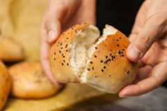 Brood in handen van vrouw de hand die van de bakker vers gebakken sesambroodje breken stock afbeelding