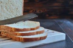 Brood met boter en mes op houten raad stock afbeeldingen