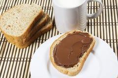 Brood met chocolade uitgespreide melk en hazelnoten Stock Foto's