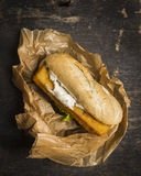 Brood met vissen en saus in een document op een houten hoogste mening als achtergrond Stock Foto