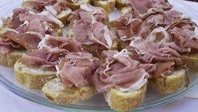 Brood in plakken met ruwe ham van San Daniele wordt gesneden die royalty-vrije stock foto's