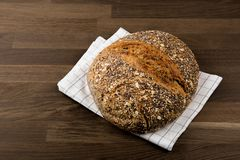 Brood, Vers Gezond Donker die Brood met Zaden op keukenhanddoek wordt behandeld, houten achtergrond stock foto