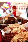 Brood vrouw-verkoper op het vierkant met close-up van rond brood, brood stock afbeelding