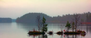 Quiet sad fall day on quiet lake. Brooding landscape with islets. Quiet sad fall day on serene lake, fog light stock images