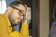 Brooding, unshaven man with glasses and a laptop at home. royalty free stock photos