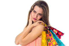 Brooding young girl keeps on shoulder bags from stores isolated  white background Stock Photography