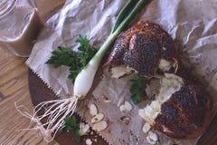 Broodje met kaas met papaverzaden wordt in document op a worden verpakt bestrooid die Royalty-vrije Stock Afbeelding