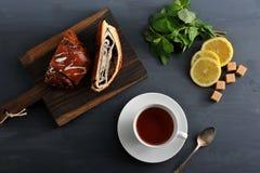 Broodje met papaverzaden, thee, citroen en munt op houten achtergrond stock fotografie