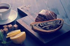 Broodje met papaverzaden, thee, citroen en munt op houten achtergrond royalty-vrije stock fotografie