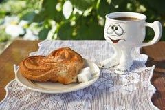 Broodje met suiker op een plaat en koffie in een kop Stock Afbeelding