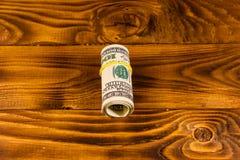 Broodje van de honderd dollarsrekeningen met rubber op houten lijst stock afbeeldingen