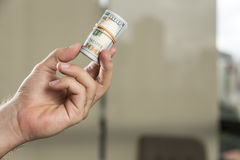 Broodje van 100 dollarsrekeningen in een mensen` s hand Stock Foto's