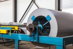 Broodje van gegalvaniseerd staal of metaal op machine in industriële workshop over walserij, de fabriek van de productiemetaalbew stock fotografie