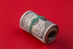 Broodje van honderd dollarsrekeningen met rubber op rode lijst royalty-vrije stock afbeelding