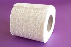 Broodje van toiletpapier op een purpere achtergrond Stock Fotografie
