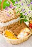 Broodjes in een rieten mand en een boeket van gebiedsbloemen Stock Afbeeldingen