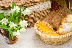 Broodjes in een rieten mand en een boeket van jasmijnbloemen Stock Fotografie
