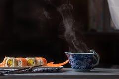 Broodjes met vissen en het stomen van thee in een kop Comfortabele avond stock afbeelding