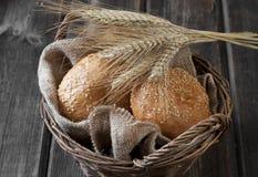 Broodjes in rieten mand op rustieke lijst Stock Foto's