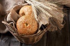 Broodjes in rieten mand op rustieke lijst Stock Fotografie