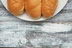 Broodjesbroden voor Ontbijt of voor het Voorbereiden van Hotdogs Grijze oude houten achtergrond Witte plaat Exemplaarruimte voor  royalty-vrije stock afbeelding
