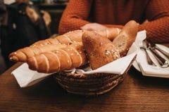 Broodmand met artisanaal brood op een lijst stock afbeeldingen