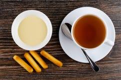 Broodstokken, kom met condens, lepel, thee in kop op sau royalty-vrije stock foto