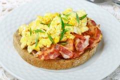 Broodtoost met roereieren, gebraden bacon en groen uienclose-up royalty-vrije stock foto's