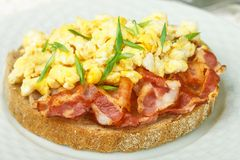 Broodtoost met roereieren, gebraden bacon en groen uienclose-up stock fotografie