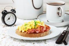 Broodtoost met roereieren, gebraden bacon en groene uien royalty-vrije stock afbeeldingen