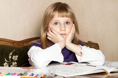 A broody blond child. A broody blond girl with felt-tip pens Royalty Free Stock Image