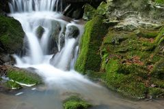 Brook. With small waterfall and stones with moss stock image