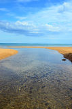 Brook flowing across the beach and outfalls into t Royalty Free Stock Images