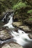 Brook flowing from waterfall. Brook flowing on rock mass from waterfall in vertical composition Stock Photos