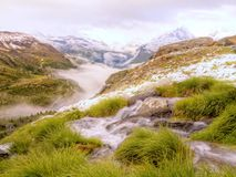 Brook in fresh Alps meadow, snowy peaks of Alps in background. Cold misty and rainy weather in mountains at the end of fall. Brook in fresh green Alps meadow stock photos