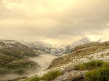 Brook in fresh Alps meadow, snowy peaks of Alps in background. Cold misty and rainy weather in mountains at the end of fall. Stock Photos