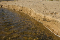Brook tempted sandy beach. The creek was formed as a result of prolonged rains. Fast water easily erodes the soft sand on the way to the ocean Royalty Free Stock Image
