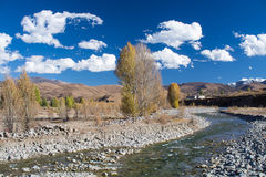 Brook with trees in autumn and mountains with blue sky backgroun Stock Photo