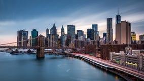 Brooklyn-Brücke und der Finanzbezirk an der Dämmerung Lizenzfreie Stockfotografie