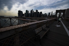 Brooklyn Bridge. Manhattan skyline with clouds shot from the Brooklyn Bridge with one female walking - New York 2007 Stock Photography