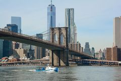 Brooklyn Bridge and a boat. Sailing in the East river in New York City Stock Photo