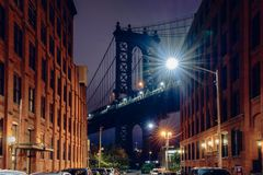 Brooklyn bridge. Seen from a narrow alley enclosed by two brick buildings at dusk, NYC USA royalty free stock images