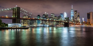 Brooklyn Bridge and the Financial District`s skyscrapers at twilight with light clouds. New York City Stock Photos