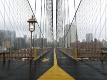 Brooklyn Bridge Fog. Brooklyn bridge walkway on a quiet foggy morning Stock Image