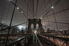 Brooklyn Bridge during a foggy night in New York Stock Images