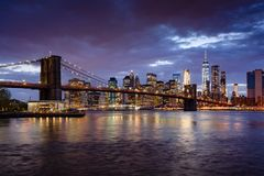 Brooklyn Bridge and Lower Manhattan skyscrapers at dusk with the East River. Manhattan, New York City stock photo