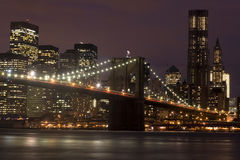 Brooklyn Bridge Manhattan. The iconic Brooklyn Bridge blends into the skyscrapers and office buildings of lower Manhattan at night royalty free stock image
