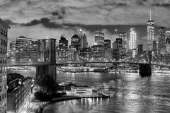 Brooklyn Bridge and Manhattan at night. Black and white photo of Brooklyn Bridge and Manhattan with visible waxing crescent moon at night, New York City, USA Royalty Free Stock Photo