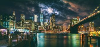 New York City Brooklyn Bridge and Manhattan skyline illuminated at night with full moon overhead. stock photos