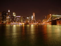 Brooklyn Bridge and Manhattan skyline by night. Shiny water of hudson riverat the foreground. At the background is Brooklyn Bridge and Manhattan skyline Stock Images